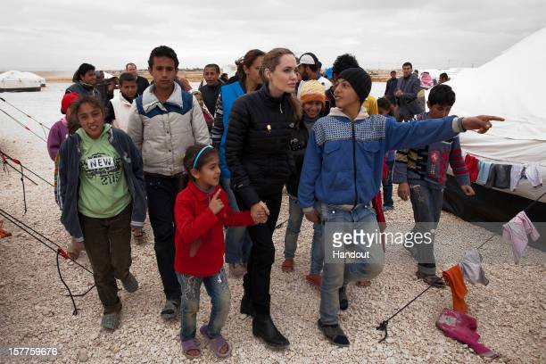 In this handout image provided by UNHCR, UNHCR Special Envoy Angelina Jolie meets with refugees at the Zaatari refugee camp on December 6, 2012...