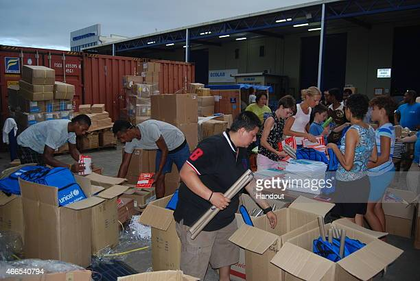 In this handout image provided by UNICEF volunteers pack school bags at UNICEF's Pacific regional warehouse for children affected by tropical Cyclone...
