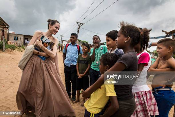 In this handout image provided by United Nations High Commission for Refugees, UNHCR Special Envoy Angelina Jolie speaks with children in Riohacha,...