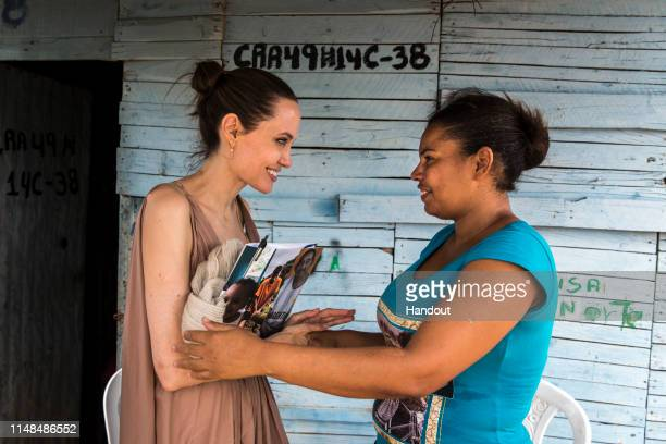 In this handout image provided by United Nations High Commission for Refugees UNHCR Special Envoy Angelina Jolie speaks with Yoryanis Ojeda on June 7...