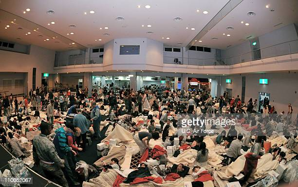 In this handout image provided by U.S. Air Force, American Red Cross volunteers provide blankets and pillows to passengers of a commercial airline...