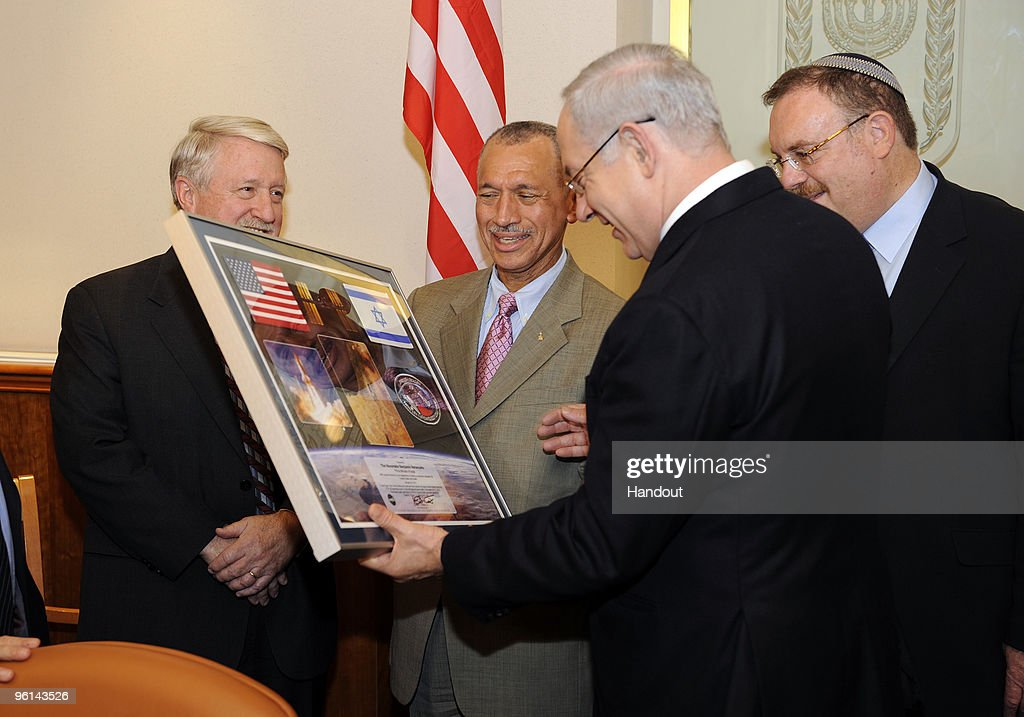 In this handout image provided by U.S. Embassy Tel-Aviv, NASA Administrator Charles F. Bolden, Jr. (2L) presents a photo montage to Israeli Prime Minister Benjamin Netanyahu (2R) with flags of the USA and Israel and mission patch January 24, 2010 in Jerusalem, Israel. These flags of the United States and Israel were flown aboard the Space Shuttle Atlantis during the STS-129 assembly mission to the international space station. November 16-27, 2009. The mission patch was flown on STS-J1, space shuttle Discovery, piloted by Charles F. Bolden, Jr. April 24 - 29, 1990. They met to discuss past and future bilateral cooperation in space science research and exploration.