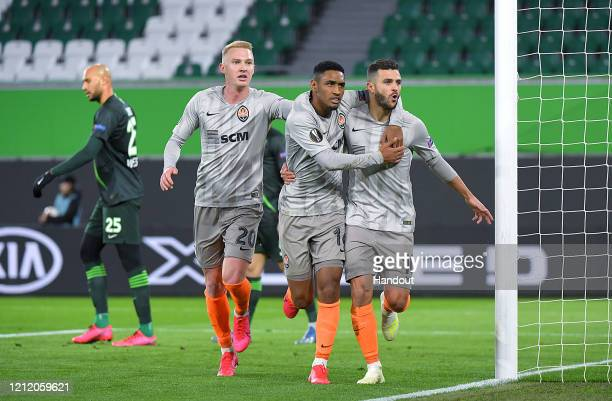 In this handout image provided by VfL Wolfsburg Junior Moraes of Shakhtar Donetsk celebrates with Tete and Viktor Kovalenko after scoring his team's...