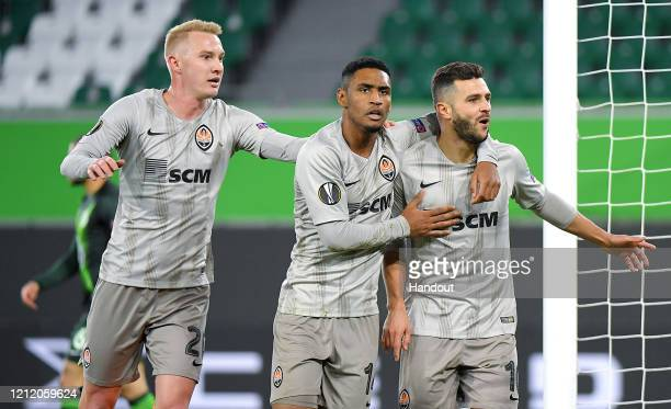 In this handout image provided by VfL Wolfsburg, Junior Moraes of Shakhtar Donetsk celebrates with Tete and Viktor Kovalenko after scoring his team's...