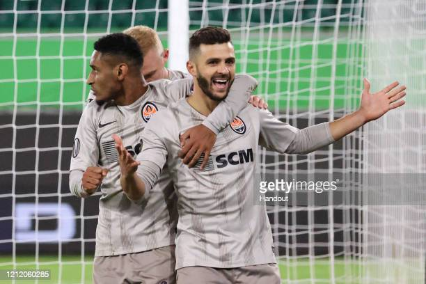 In this handout image provided by VfL Wolfsburg, Junior Moraes of Shakhtar Donetsk celebrates with his team mates after scoring his team's first goal...
