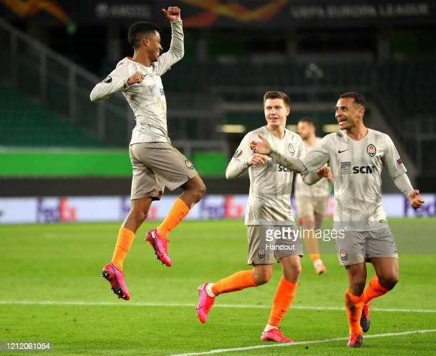 In this handout image provided by VfL Wolfsburg, Marcos Antonio of Shakhtar Donetsk celebrates with his team mates after scoring his team's second...