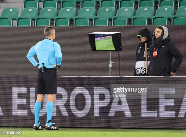 In this handout image provided by VfL Wolfsburg, Referee Damir Skomina checks the VAR screen during the UEFA Europa League round of 16 first leg...