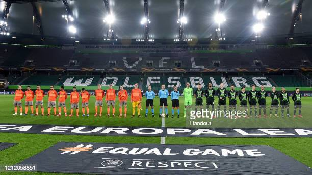 In this handout image provided by VfL Wolfsburg, The two teams line up prior to the UEFA Europa League round of 16 first leg match between VfL...