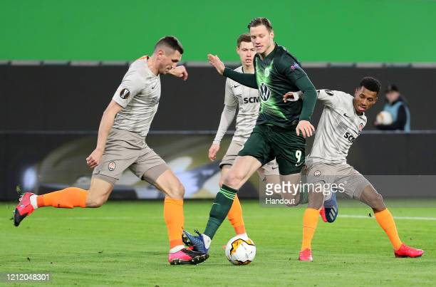 In this handout image provided by VfL Wolfsburg, Wout Weghorst of VfL Wolfsburg is tackled during the UEFA Europa League round of 16 first leg match...