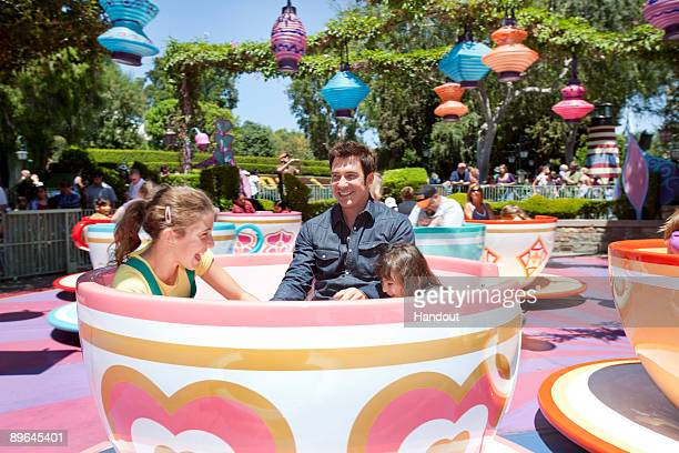 In this handout image provided by Walt Disney Studios Dylan McDermott star of the new hit TNT drama Dark Blue rides the Mad Tea Party with daughters...