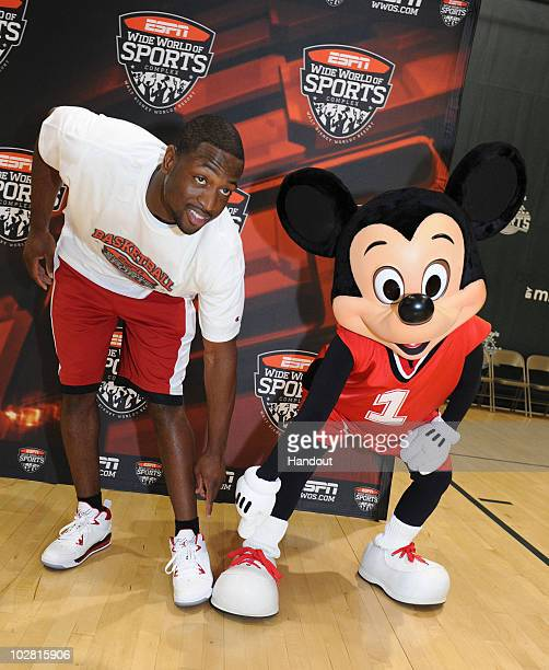 In this handout image provided by Walt Disney Studios, Miami Heat guard Dwyane Wade compares basketball shoes with Mickey Mouse July 11, 2010 at the...