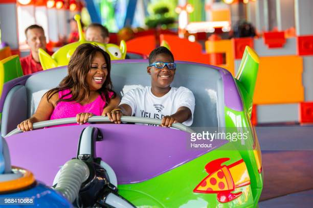 In this handout image provided by Walt Disney World Resort actress Sherri Shepherd and her son Jeffrey take a spin aboard Alien Swirling Saucers...