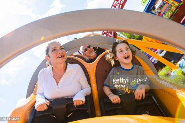 In this handout image provided by Walt Disney World Resort, Gloria Estefan, Emilio Estefan and their grandson, Sasha, enjoy Slinky Dog Dash coaster...