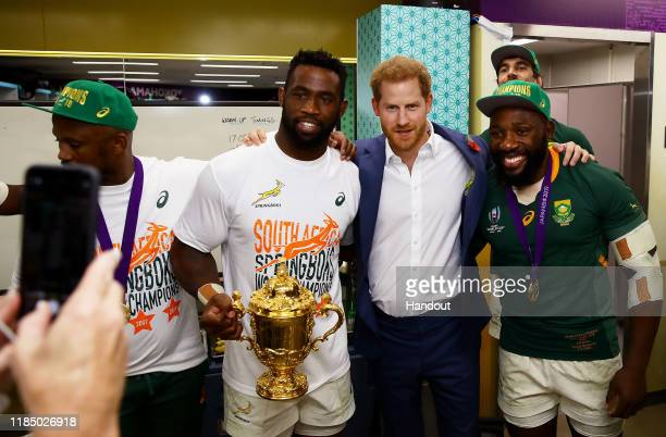 In this handout image provided by World Rugby Prince Harry Duke of Sussex pose for a photo with Siya Kolisi of South Africa holding the Web Ellis cup...