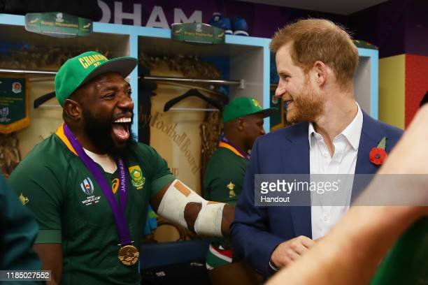 In this handout image provided by World Rugby Prince Harry Duke of Sussex shares a joke with Tendai Mtawarira of South Africa following his team's...