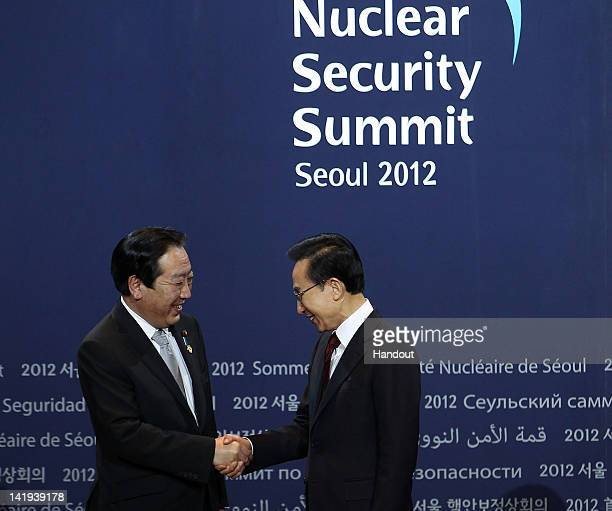 In this handout image provided by Yonhap News Japanese Prime Minister Yoshihiko Noda and South Korean President Lee Myungbak shake hands prior to the...