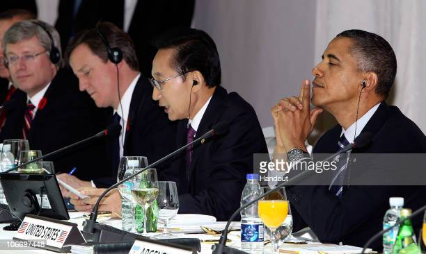 In this handout image provided by Yonhap News US President Barack Obama listens as South Korean President Lee Myungbak makes a welcome speech during...