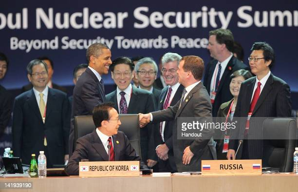 In this handout image provided by Yonhap News US President Barack Obama and Russian President Dmitry Medvedev shake hands prior to the 2012 Seoul...