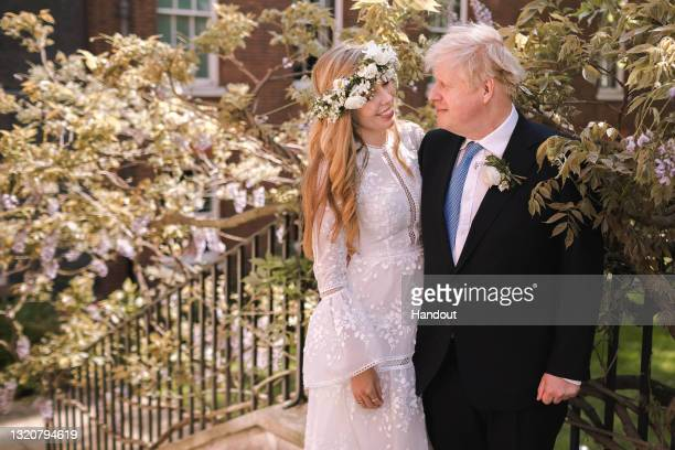 In this handout image released by 10 Downing Street, Prime Minister Boris Johnson poses with his wife Carrie Johnson in the garden of 10 Downing...