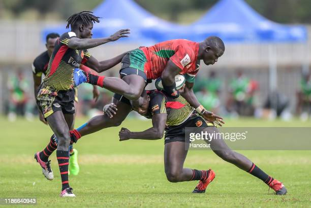 In this handout image released by APO Group Andrew Amonde of Kenya is tackled Ofoyrwoth Aaron and Munyani Ian of Uganda during the Rugby Africa The...