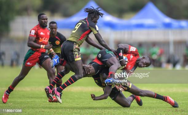In this handout image released by APO Group Andrew Amonde of Kenya is tackled by Ofoyrwoth Aaron and Munyani Ian of Uganda during the Rugby Africa...