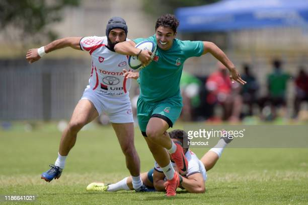 In this handout image released by APO Group Cliaws Khalife of Tunisia escapes the tackle from El Arrouchi Marouane of Morocco during the Rugby Africa...