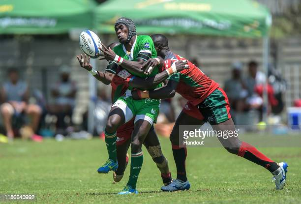 In this handout image released by APO Group Herizo Rasoanaivo of Madagascar passes as he ia tackled by Jeffrey Oluoch of Kenya during the Rugby...