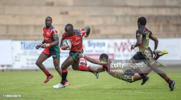 In this handout image released by APO Group Jeffrey Oluoch of Kenya evades the tackle from Kasito Adrian of Uganda during the Rugby Africa The Africa...