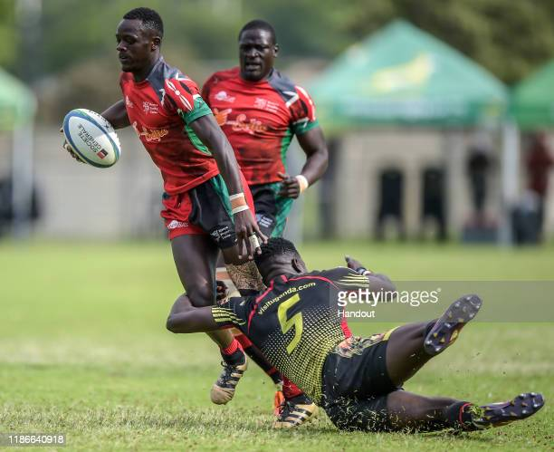 In this handout image released by APO Group Johnston Olindi of Kenya is tackled by Wokorach Philip of Uganda during the Rugby Africa The Africa Men's...