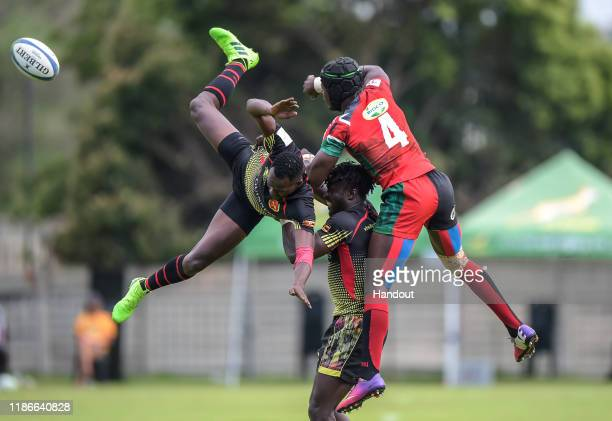 In this handout image released by APO Group Massangananzia Isaac of Uganda Ogena Pius of Uganda and Vincent Onyala of Kenya compete for the ball...