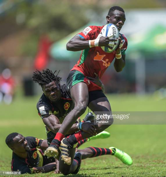 In this handout image released by APO Group Massangananzia Isaac of Uganda is tackled by Johnston Olindi of Kenya during the Rugby Africa The Africa...