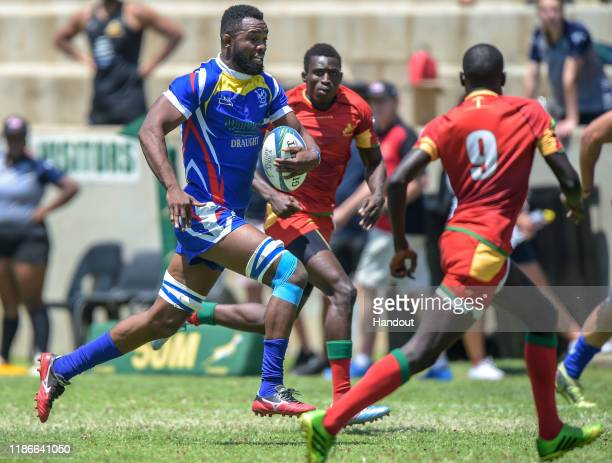 In this handout image released by APO Group Muharua Katjijeko of Namibia is closed down by Sall Mansour of Senegalduring the Rugby Africa The Africa...