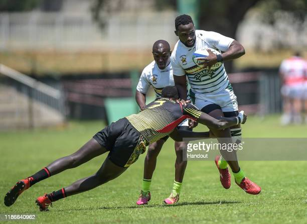 In this handout image released by APO Group Njabula Ndlovu of Zimbabwe is tackled by Wokorach Philip of Uganda during the Rugby Africa The Africa...