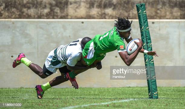 In this handout image released by APO Group Solomampionona Maminandrasan of Madagascar scores a try despite the tackle from Stephan Hunduza of...
