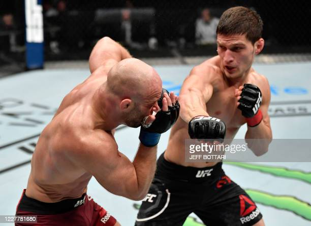 In this handout image released by the Ultimate Fighting Championship , Movsar Evloev of Russia punches Mike Grundy of England in their featherweight...