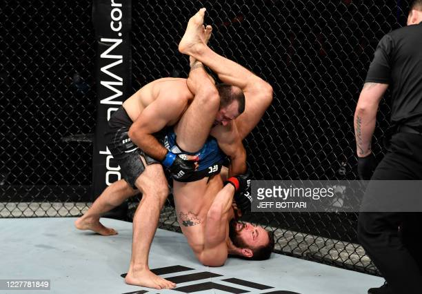 In this handout image released by the Ultimate Fighting Championship , Paul Craig of Scotland attempts to secure a triangle choke against Gadzhimurad...