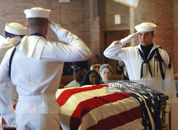 In this handout image released by the US Navy Commander Navy Region MidAtlantic Honor Guard salute as they bring retired Master Chief Boatswain's...