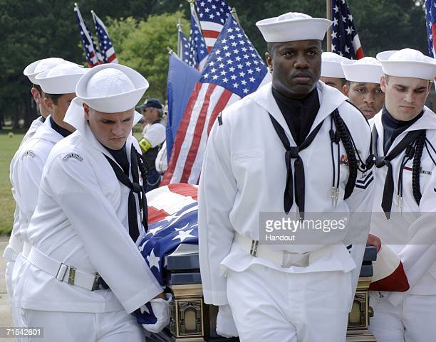 In this handout image released by the US Navy members of the Commander Navy Region MidAtlantic Honor Guard carry retired Master Chief Boatswain's...