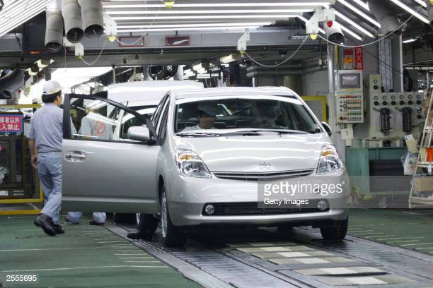 In this handout image released by Toyota Motor Corporation Toyota employees check the newgeneration Prius hybrid for final inspection at Toyota's...