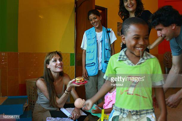In this handout image released June 18 by the UNHCR, Goodwill Ambassador Angelina Jolie speaks with kids during her visit in a daycare centre run by...