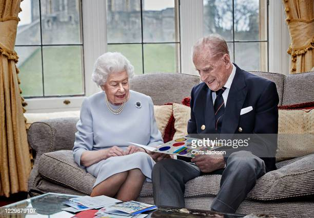 In this handout image released on November 19, Queen Elizabeth II and Prince Philip, Duke of Edinburgh look at their homemade wedding anniversary...