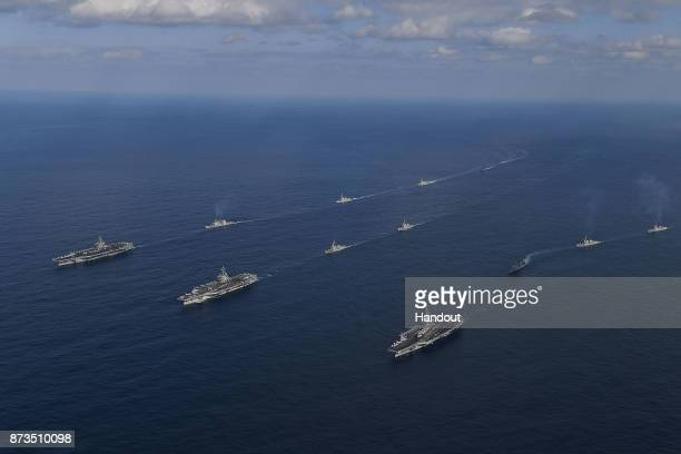 In this handout image released September 13 by South Korean Defense Ministry, USS Nimitz , USS Ronald Reagan and USS Theodore Roosevelt conducting...