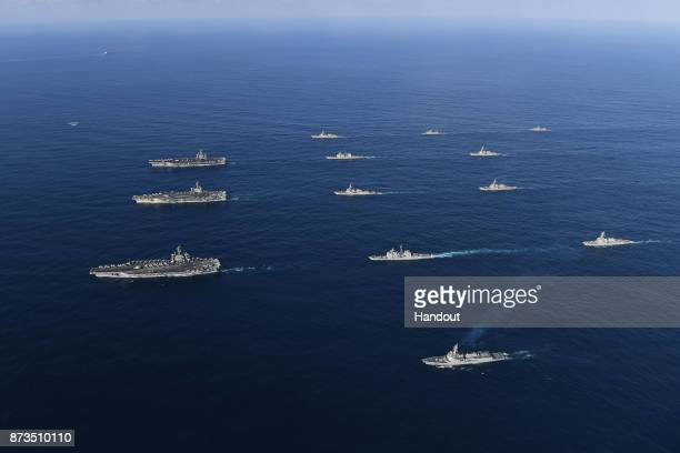 In this handout image released September 13 by South Korean Defense Ministry USS Nimitz USS Ronald Reagan and USS Theodore Roosevelt conducting...