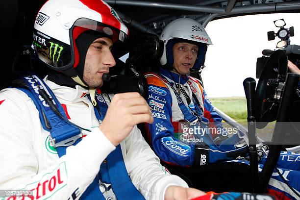 In this handout image supplied by Castrol Moto GP rider Marco Simoncelli of Italy is seen with driver Mikko Hirvonen of Finland during a oneoff test...