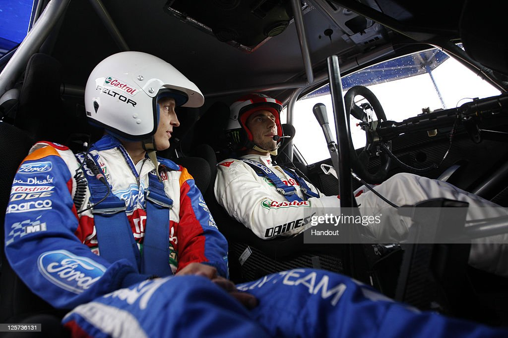 In this handout image supplied by Castrol, Moto GP rider Marco Simoncelli (R) of Italy poses with driver Mikko Hirvonen (L) of Finland during a one-off test with the Castrol sponsored Ford Abu Dhabi World Rally Team at their team base, on September 21, 2011 in Carlisle, England. The test was arranged by Castrol, who partner Simoncelli's San Carlo Honda Gresini Racing team.