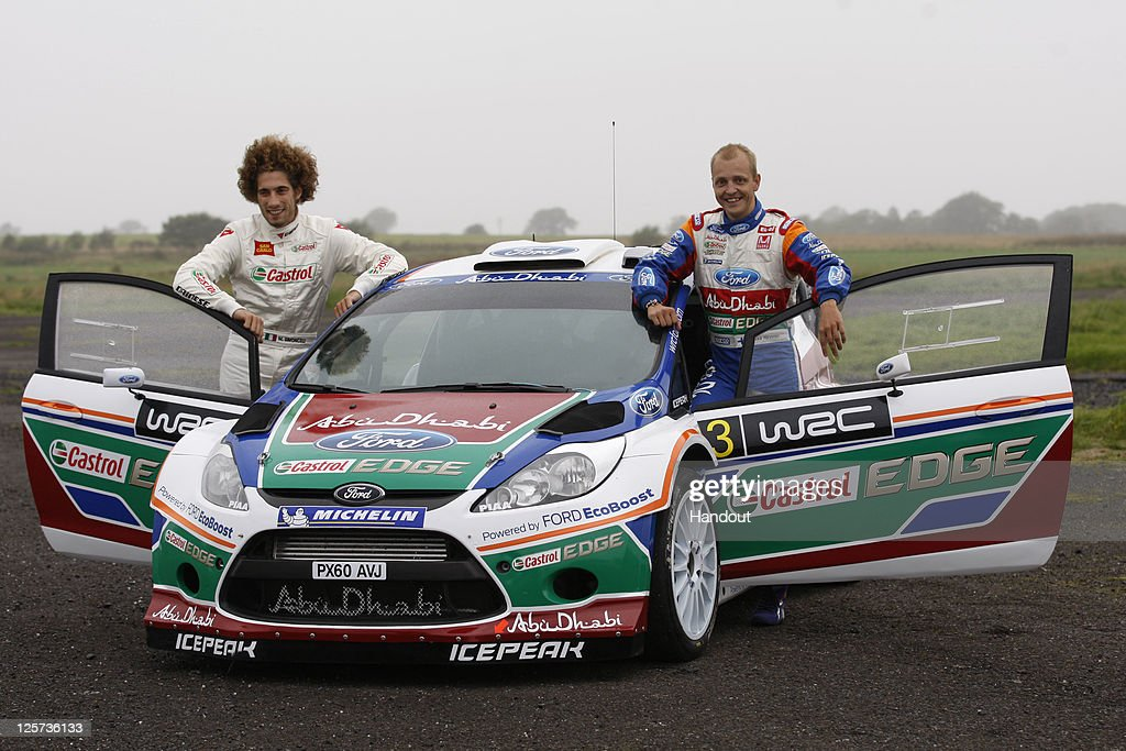 In this handout image supplied by Castrol, Moto GP rider Marco Simoncelli (L) of Italy poses with driver Mikko Hirvonen (R) of Finland during a one-off test with the Castrol sponsored Ford Abu Dhabi World Rally Team at their team base, on September 21, 2011 in Carlisle, England. The test was arranged by Castrol, who partner Simoncelli's San Carlo Honda Gresini Racing team.