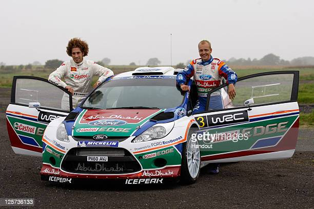 In this handout image supplied by Castrol Moto GP rider Marco Simoncelli of Italy poses with driver Mikko Hirvonen of Finland during a oneoff test...