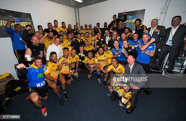 In this handout image supplied by Dave Lintott Prince Harry poses with the Hurricanes team in their changing rooms after watching the round 13 Super...
