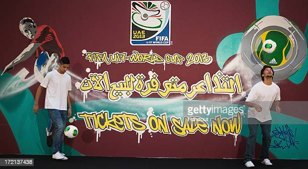 In this handout image supplied by FIFA U17 World Cup UAE 2013 UAE U17 Players Ali Ghloom and Abdulla Khathem show their skills in front of a graffiti...