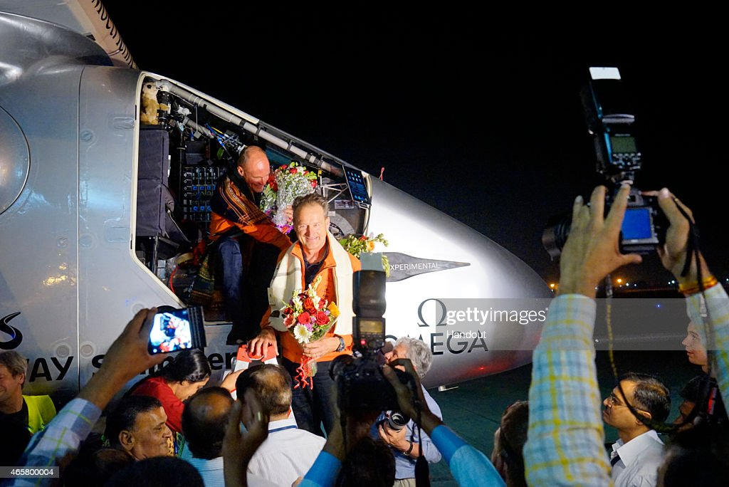In this handout image supplied by Jean Revillard, Bertrant Piccard (L) is shown after landing the Solar Impulse 2, a solar-powered airplane on the second leg of an around-the-world journey March 10, 2015 in Ahmedabad, India. With this 15:20-hour flight, Piccard set a new world record for solar distance flight with 1486 kilometers. The trip continues on March 16. The 35,000km journey is expected to last five months and is piloted by Andre Borschberg (R) and Bertrand Piccard of Switzerland. The Solar Impulse 2 is equipped with 17,000 solar cells, has a wingspan of 72 metres, and yet weighs just over 2 tonnes.